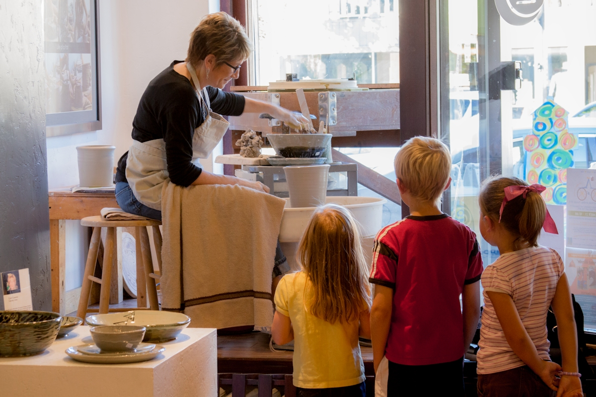 Kids talking with Cyndi as she works on potter's wheel