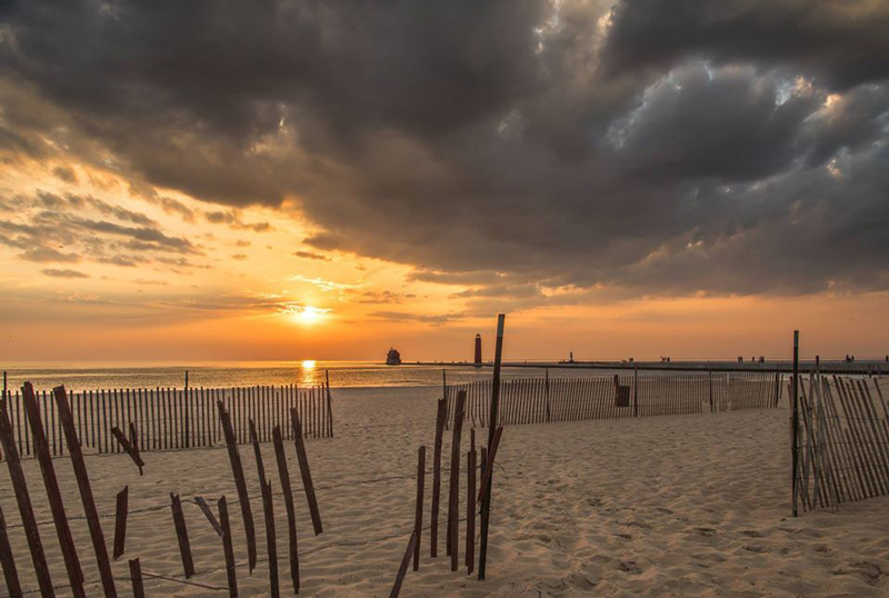 photograph of a grand haven fall sunset with snow fences in the image