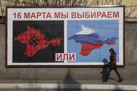 © REUTERS/Baz Ratner. A woman walking by a poster calling people to vote in the upcoming referendum, in the Crimean port city of Sevastopol March 10, 2014.