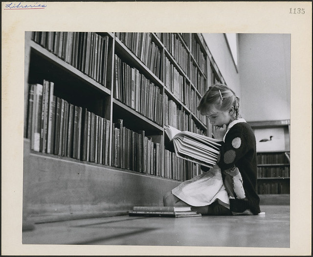 Young girl reading a book, Central Circulating Library at College and St. George Streets, Toronto, Ontario / Une jeune fille lit un livre. Bibliothèque centrale de prêt à l'intersection des rues College et Saint-George, Toronto (Ontario)