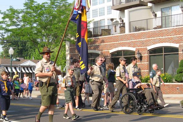 local Boy Scout troop walking down Main Street