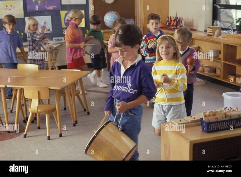 caucasian students playing instruments in montessori preschool music