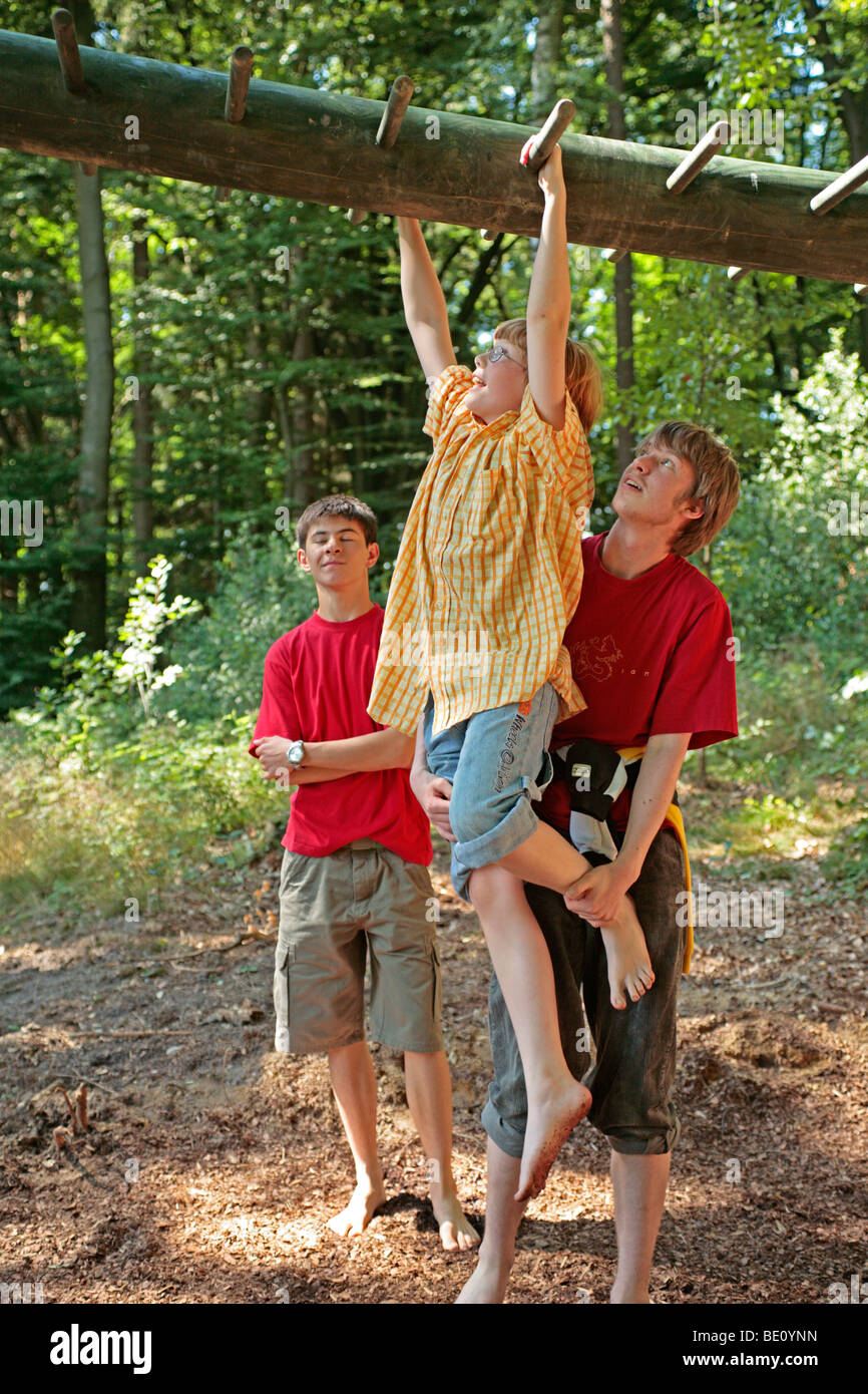 Three Teenage Boys Climbing On Monkey Bars In A Forest