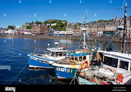 Fishing boats lined up in Oban harbour Scotland with the famous McCaig's Folly in the background Stock Photo
