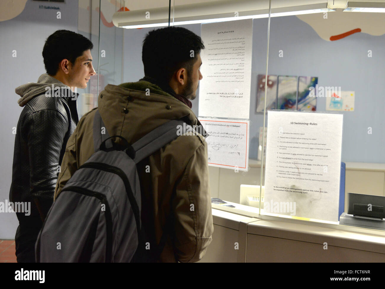 Hermeskeil, Germany. 21st Jan, 2016. Iranian refugees Mohsen and Ali (l) reading the pool rules written in German, Stock Photo