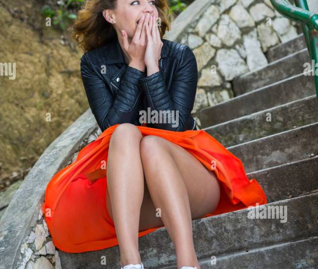Pretty Teen Girl Excited Excitement Cover Mouth With Hands In Red Skirt And Sneakers Is Shy Looking Away Outdoors Hesitate Hesitating