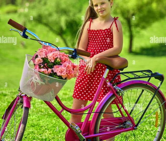 Girl Wearing Red Polka Dots Dress Rides Bicycle Into Park