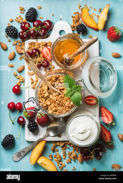 Top stock image websites. Healthy breakfast ingredients. Oat granola in open glass jar, yogurt, fruit, berries, honey and mint on white ceramic Stock Photo
