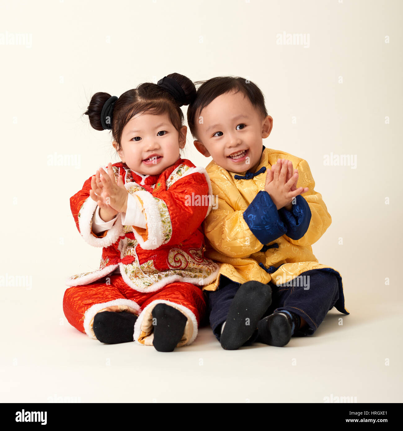 Chinese baby boy and girl in traditional Chinese New Year outfit     Chinese baby boy and girl in traditional Chinese New Year outfit  celebrating Lunar New Year