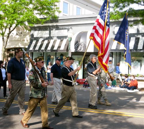 Veterans carrying flags walk down Main Street