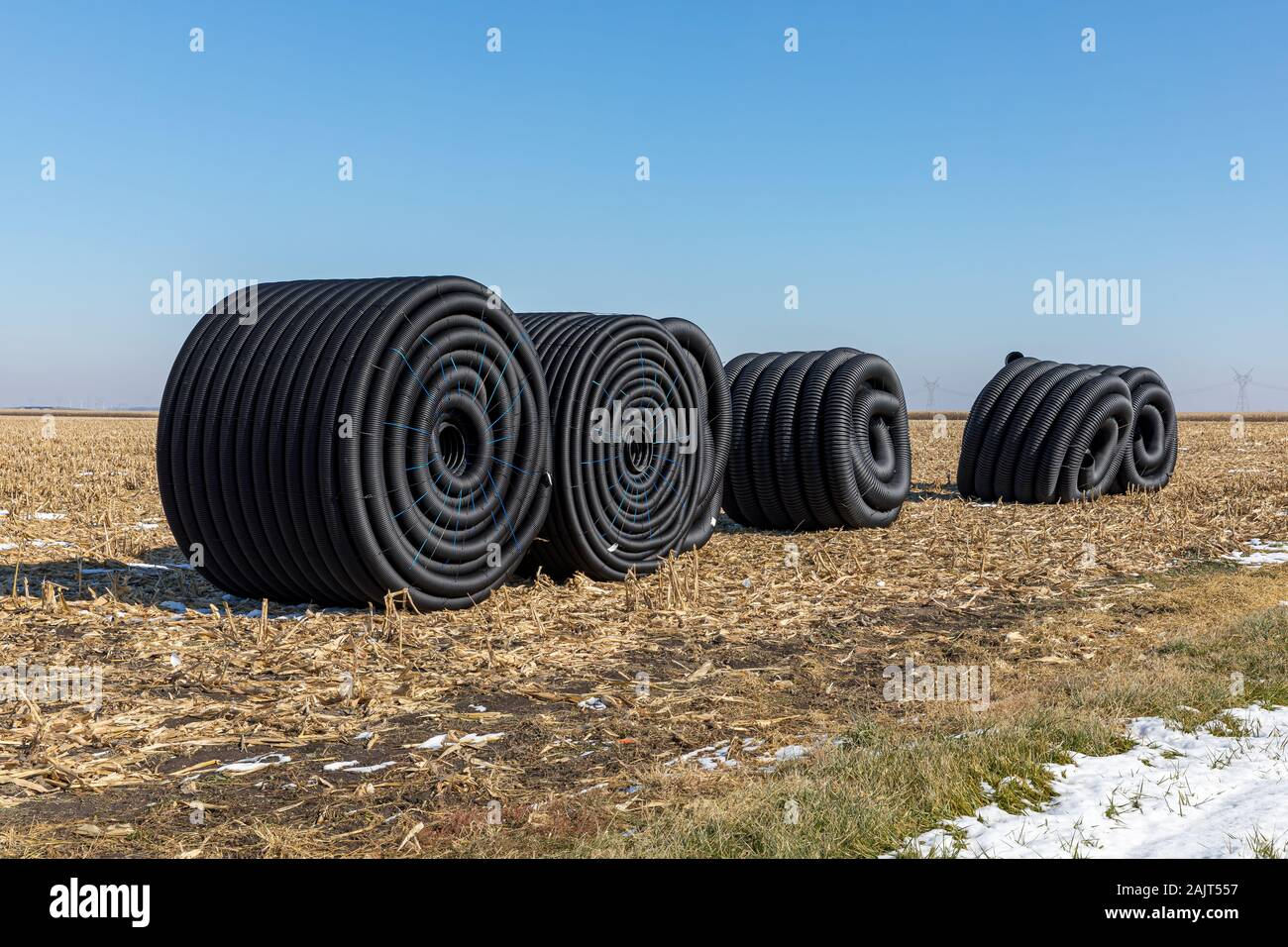 https www alamy com coiled rolls of black perforated plastic drainage pipe field tile sitting in field after harvest ready to be buried underground during winter image338591715 html