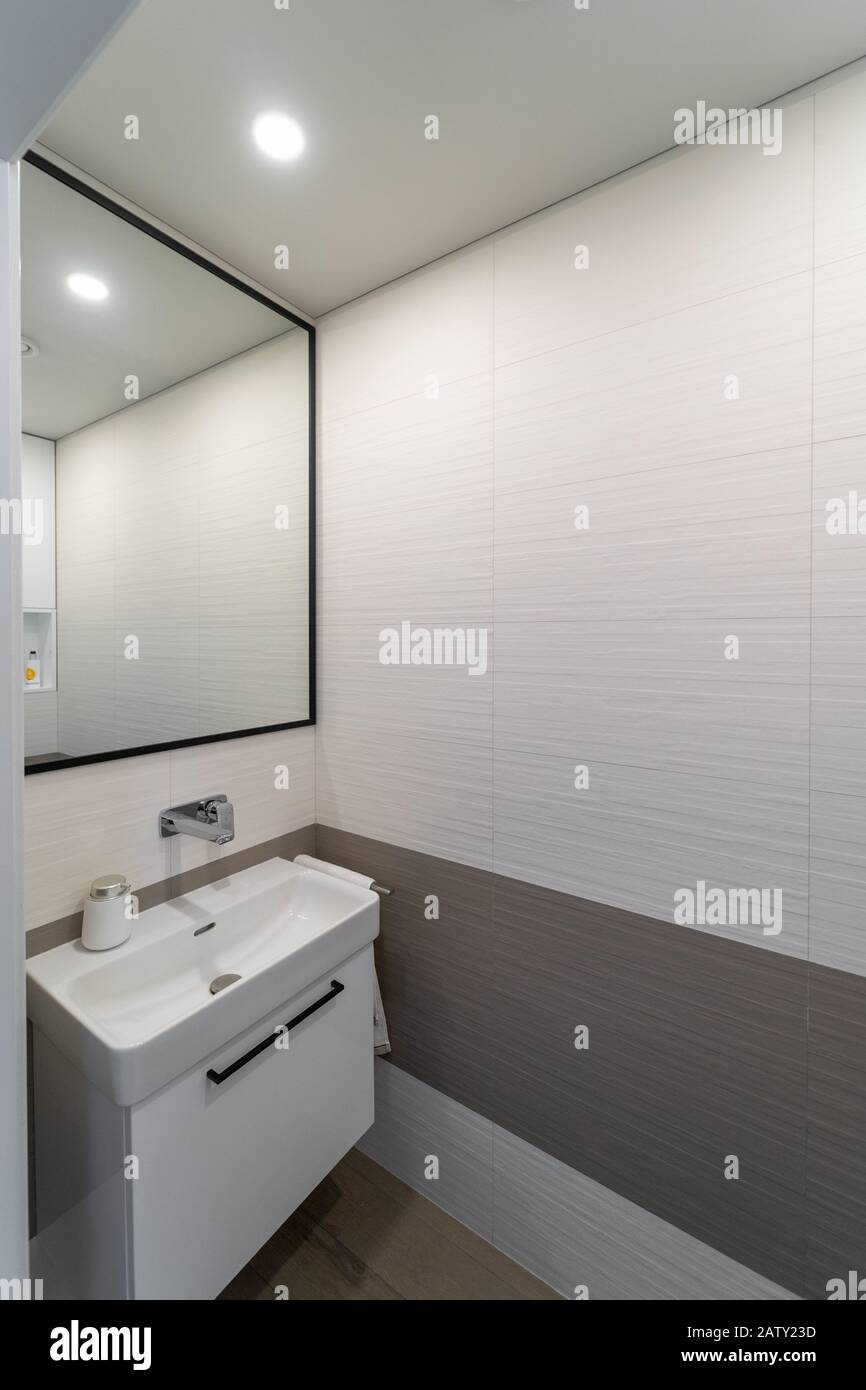 Modern New Light Colored Toilet Interior With Beige And Brown Wall And Floor Tiles White Sink On The Cupboard Next To It A Towel Hanging Above I Stock Photo Alamy