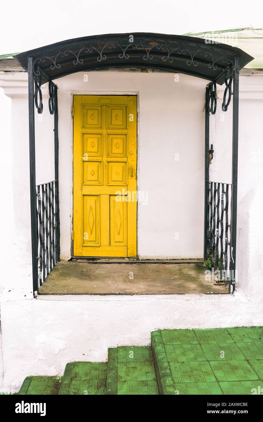 The Facade Of A Small House With White Walls A Yellow Door And A | Staircase For Small House | Internal | Popular | Tiny House | Concrete | Diy