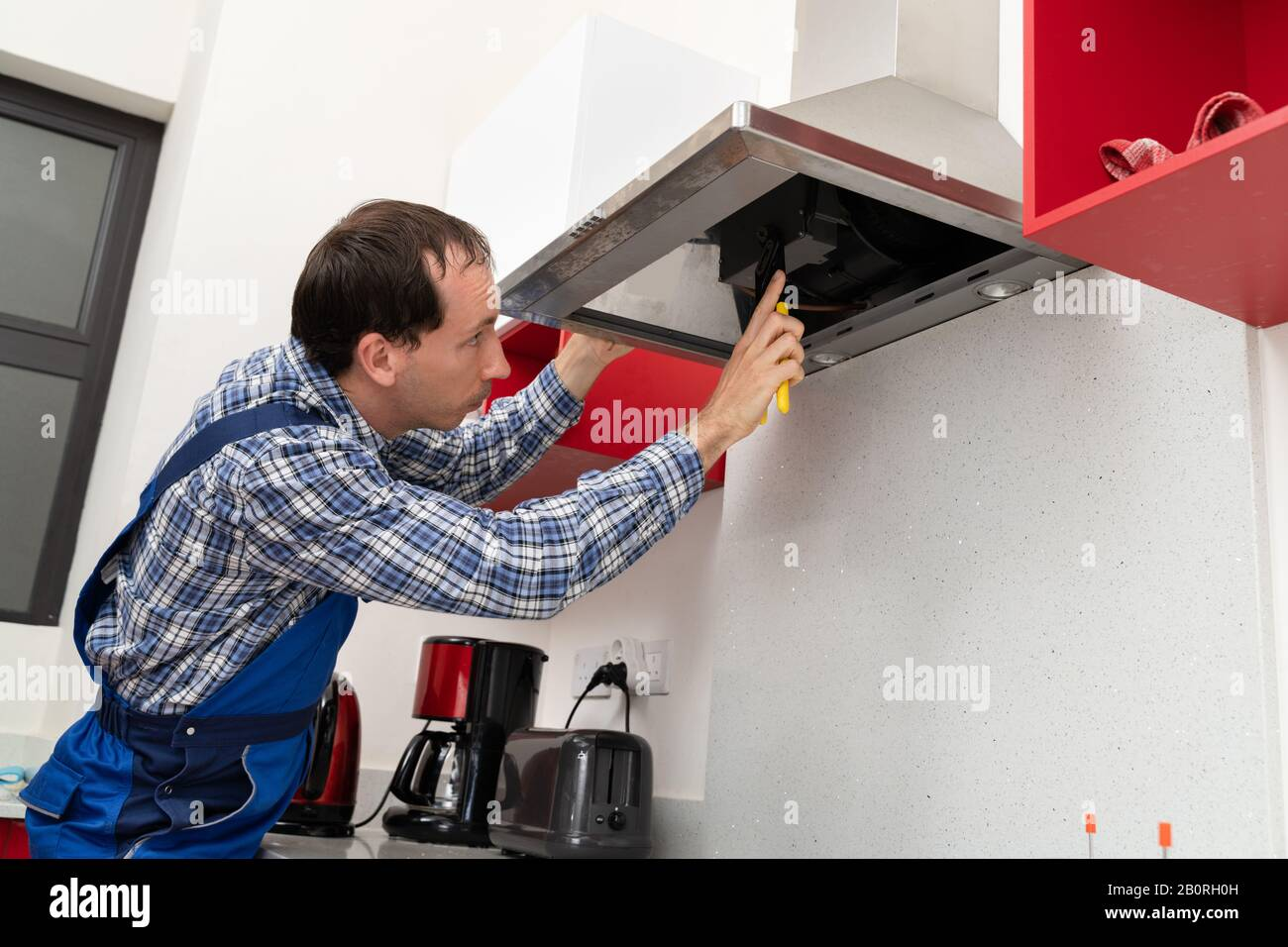 https www alamy com close up of a young male electrician repairing kitchen extractor image344725601 html