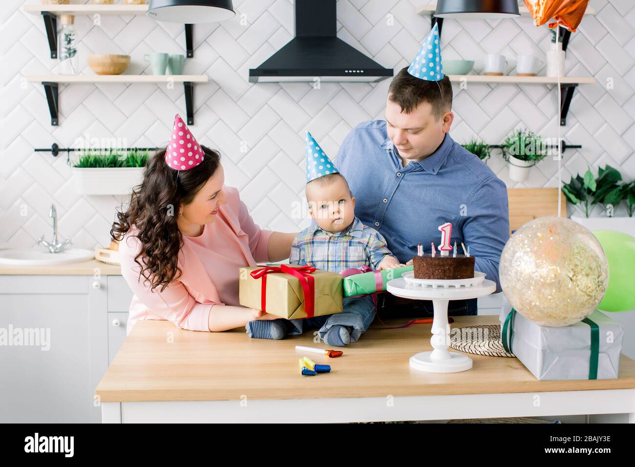 Mother And Father In Birthday Hats Celebrating First Birthday Of Baby Boy At Home Kitchen Happy Family Celebrating Birthday With A Cake Present Stock Photo Alamy
