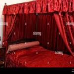 Red Upholstered Early Century Canopy Bed Stock Photo Alamy
