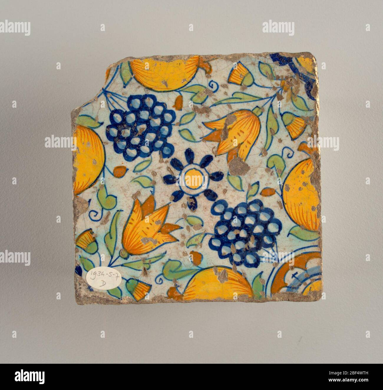 https www alamy com four tile two tiles each of a similar design in blue green and neutral yellow with fleurs de lis at four corners leaves and two small bunches of grapes in center of tiles a and b a pomegranate of tiles c and d a large bunch of grapes image353535297 html