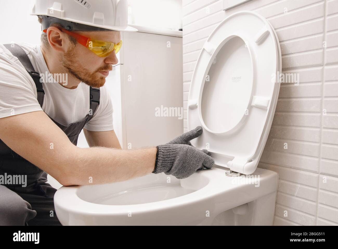 Plumber Installing Toilet Bowl In Restroom Work In Bathroom Stock Photo Alamy