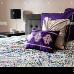 New Bed Comforter With Decorative Pattern Purple Color Pillows And Headboard In Bedroom In Staging Home House Or Apartment Modern Style With Lamp On N Stock Photo Alamy