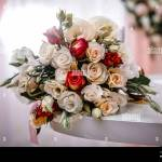 Beautiful Delicate Wedding Flower Bouquet With Roses And Ranunculuses A Gorgeous Bouquet Of White Pink And Red Roses Lies On A Table In A Room With Stock Photo Alamy