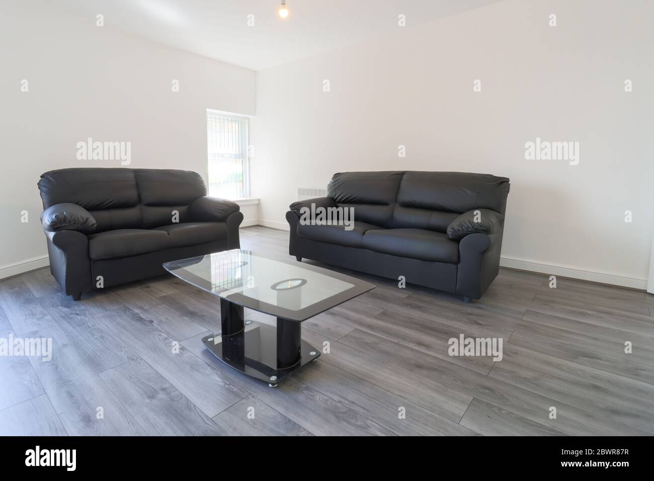 A Modern British Living Room With Two Black Leather Sofas On A Grey Wooden Floor With White Walls And Modern Blinds Up At The Window Stock Photo Alamy