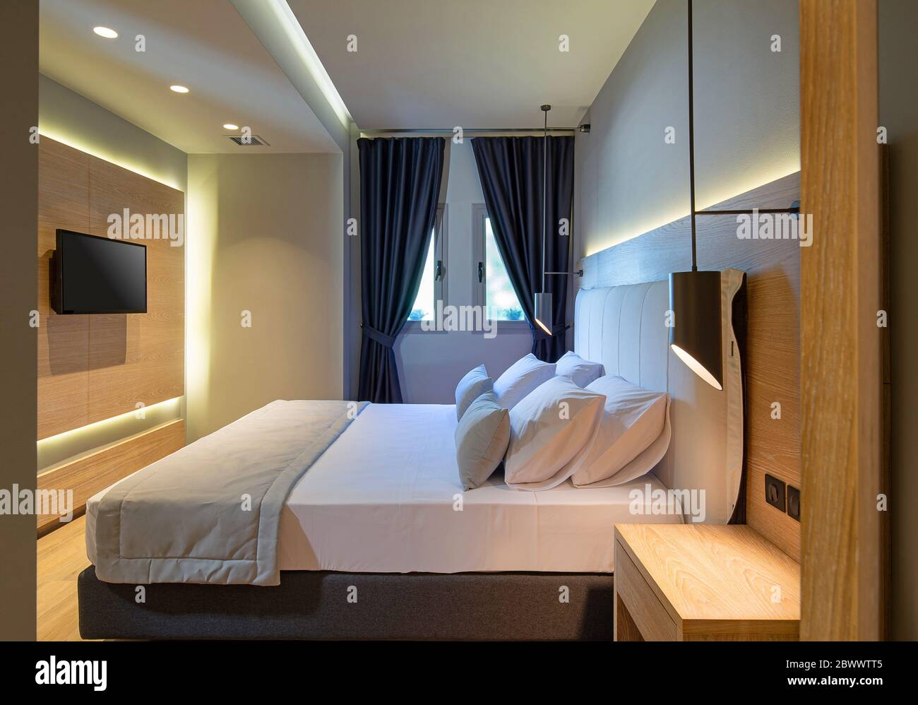 https www alamy com side view of modern bedroom interior with wooden panel flat tv backlight textile headboard stylish contemporary minimalism in hotel apartment room image360142053 html