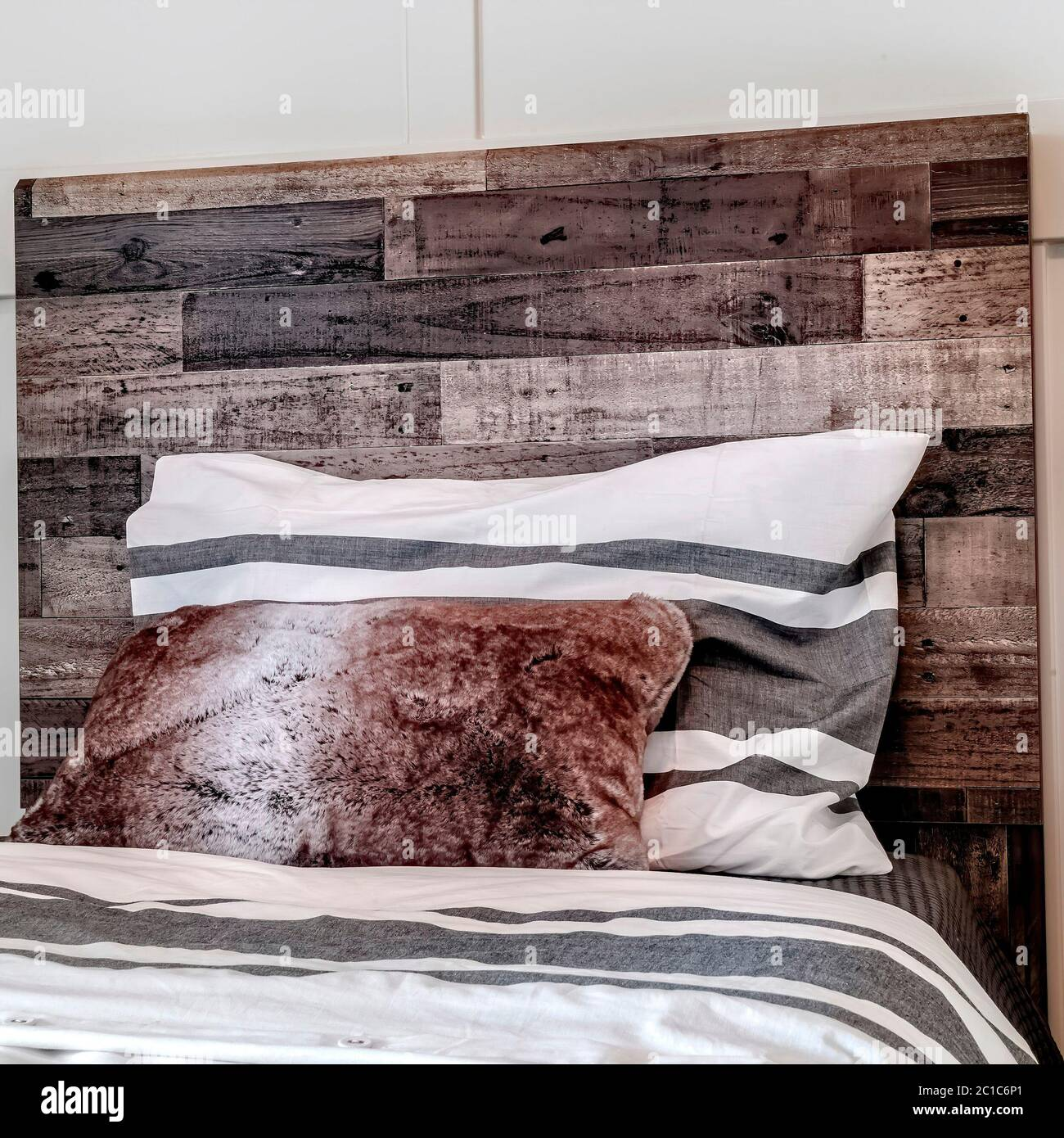 https www alamy com square frame bed with pillows against decorative wooden headboard against white panel wall image362301129 html