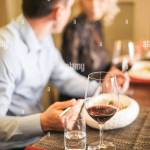 Blurred Lovely Couple Sitting In A Restaurant And Drink Wine And Tea Photos In Warm Color Shades Focus On Glass Stock Photo Alamy
