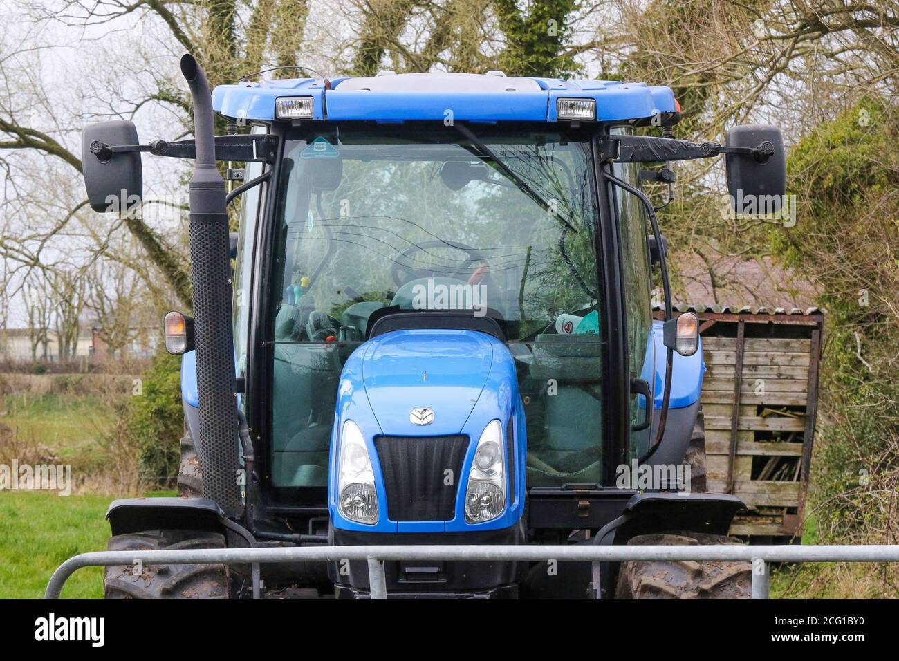 https www alamy com head on front view of blue new holland tractor cab behind metal farm gate with mirrors engine exhaust and tractor headlights all visible image371283556 html
