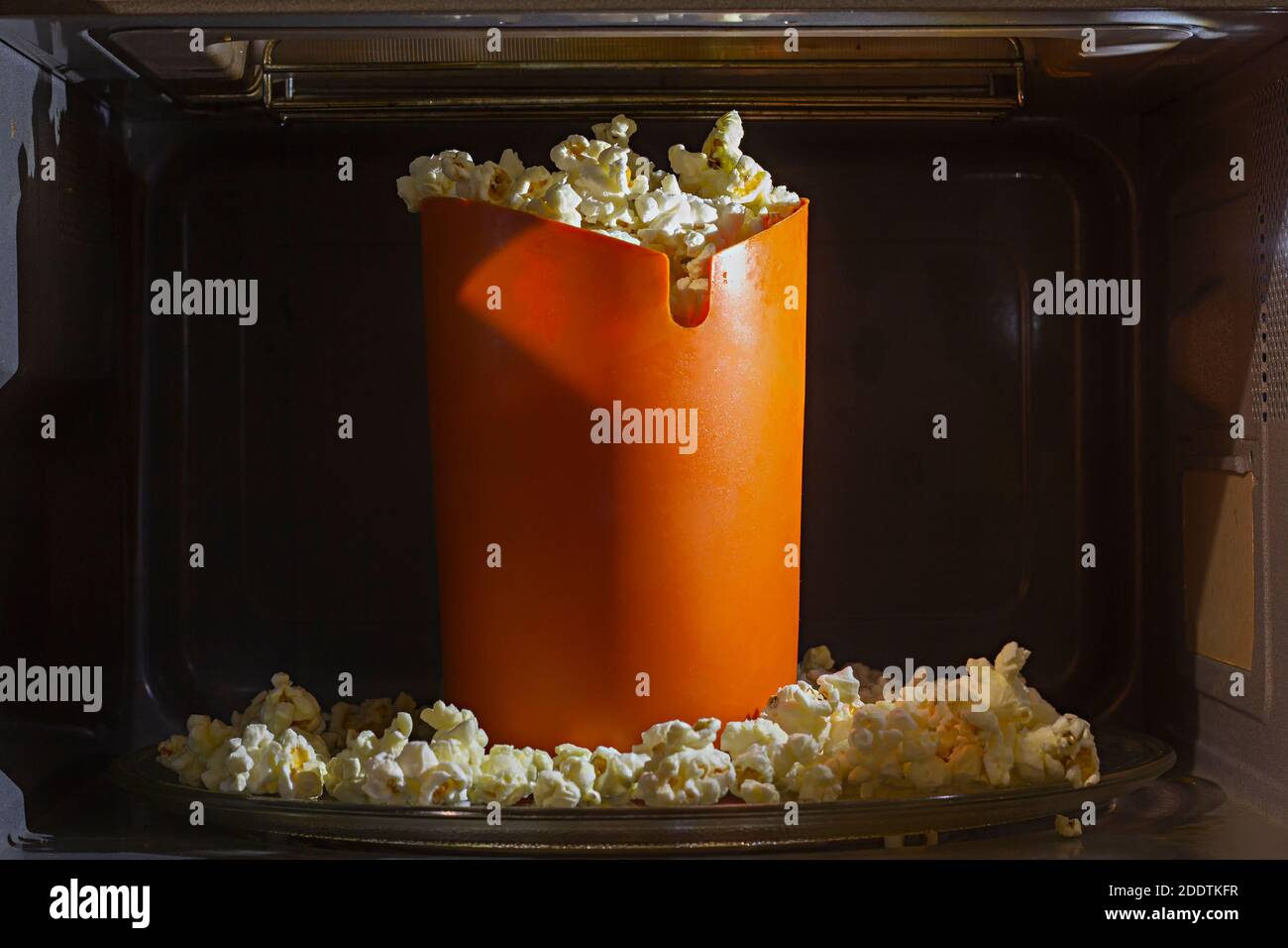 https www alamy com orange silicon bucket filled with homemade cooked popcorn inside a microwave oven special silicon bucket for popcorn microwave cooking at home image387160811 html