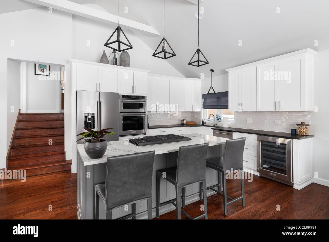 https www alamy com a beautiful white kitchen in a modern farmhouse with black lights hanging from the vaulted ceiling over the island and bar stools image401267889 html