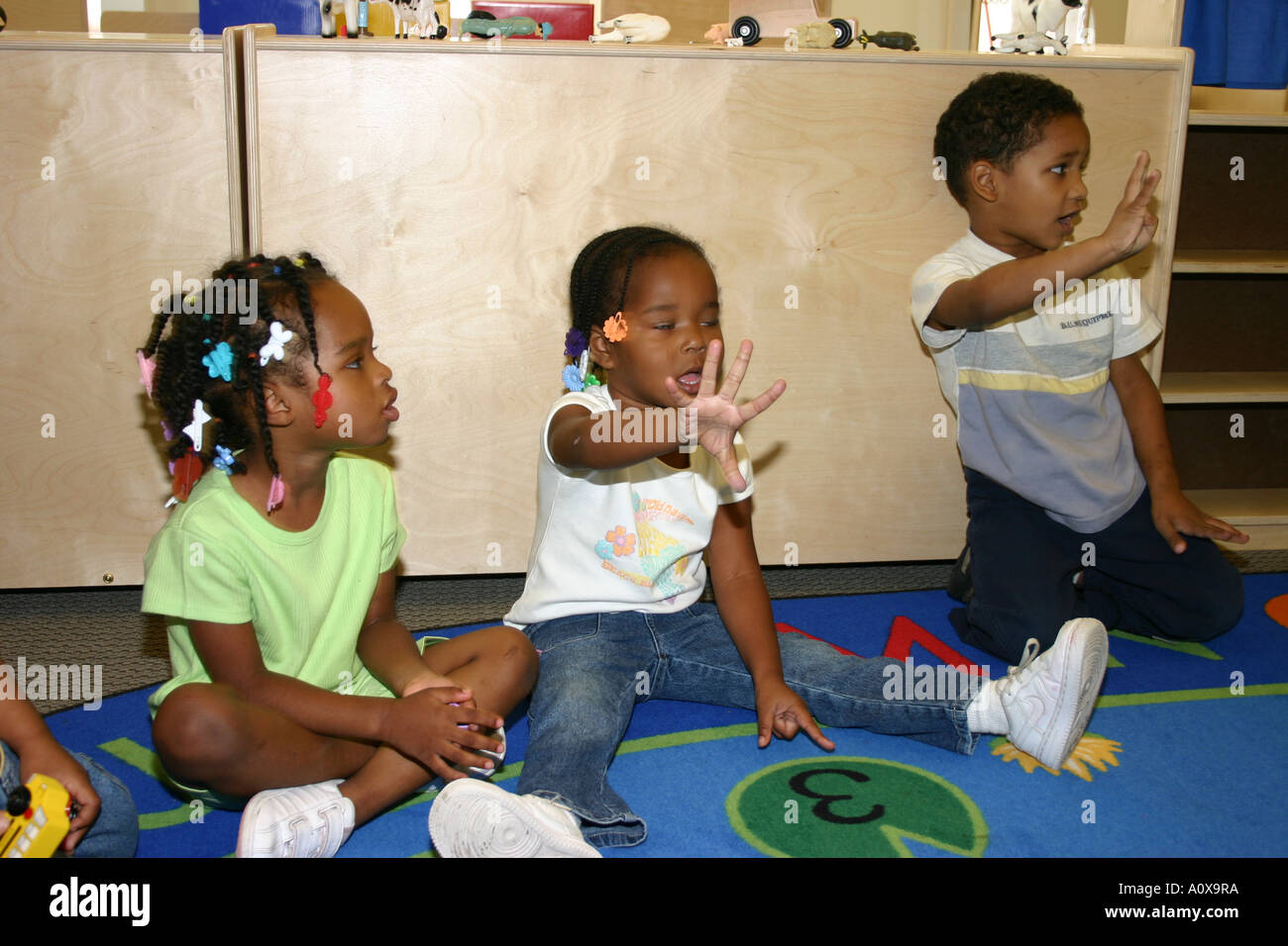 Kindergarten Teacher And Children Looking At Book Stock