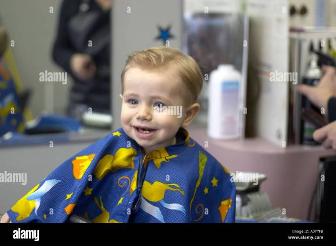 one year old boy sits in barber stool for first haircut