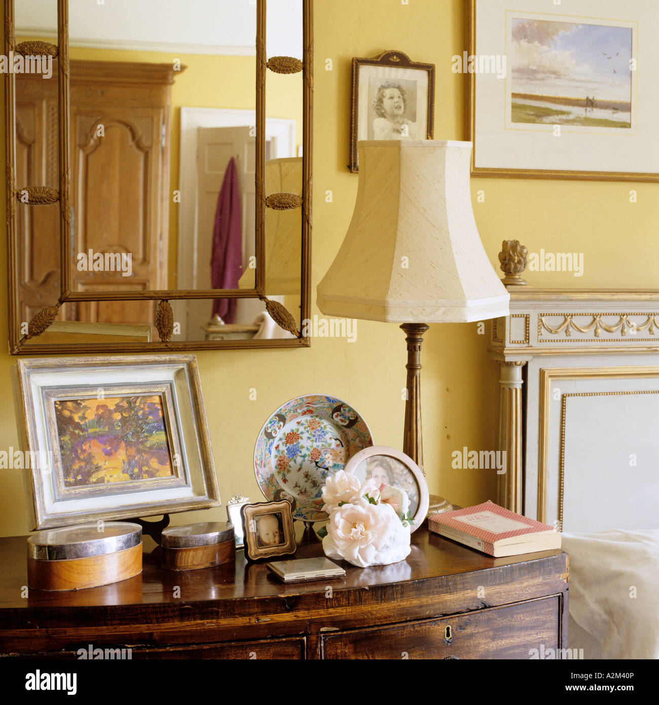 Mirror Above Bedside Table With Lamp And Ornamental Display Stock Photo Alamy