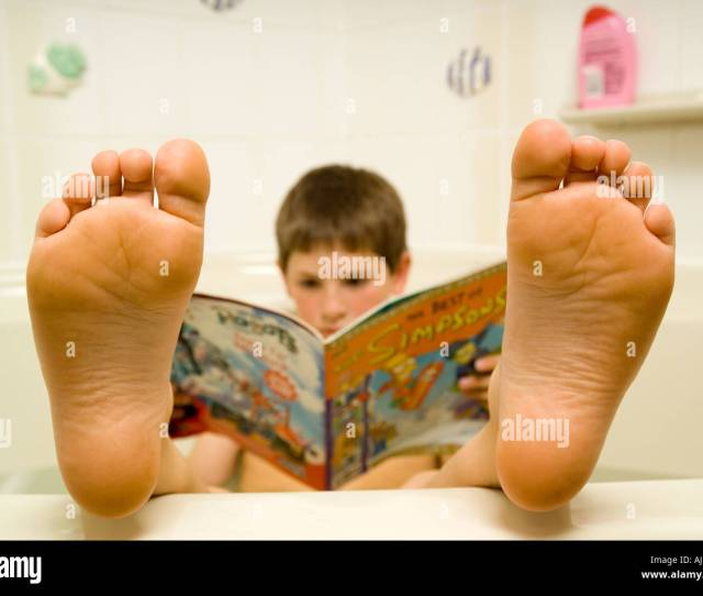 Young Boy With Feet Up In Warm Bath Reading Simpsons Magazine Showing Soles Of Feet