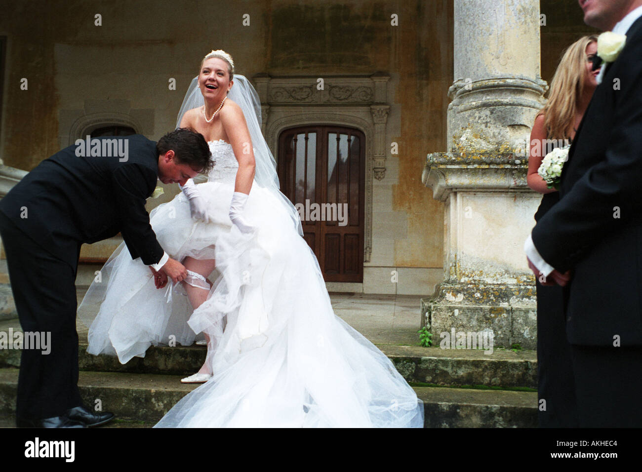 Groom Removing Smiling Bride S Garter Belt Watched By The