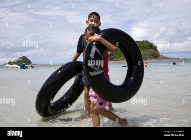 Brother And Sister Boy Girl Tubing With Inner Tubes On Sattahip Beach Near Rayong Thailand