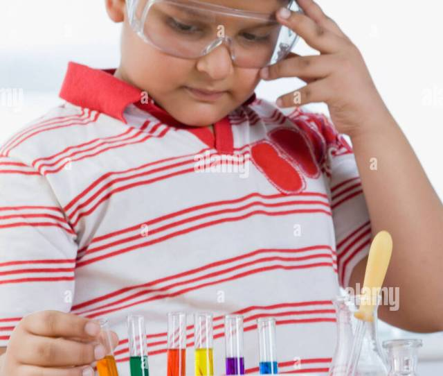 Close Up Of A Boy Picking A Test Tube From A Test Tube Holder