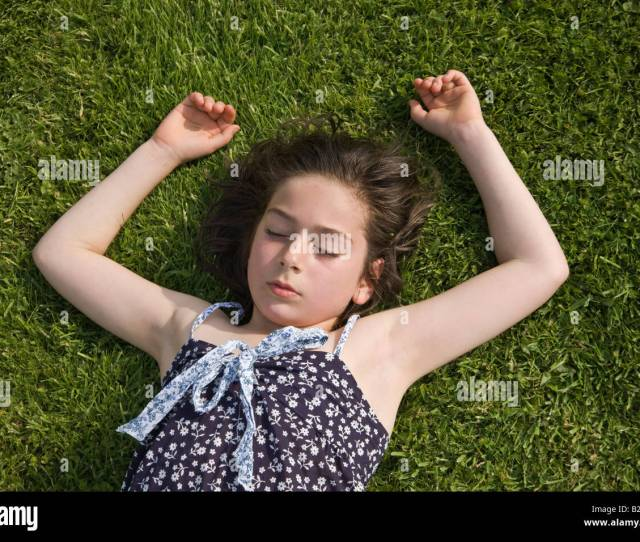 Young Girl With Eyes Closed Lying On Grass On Hot Summer Day