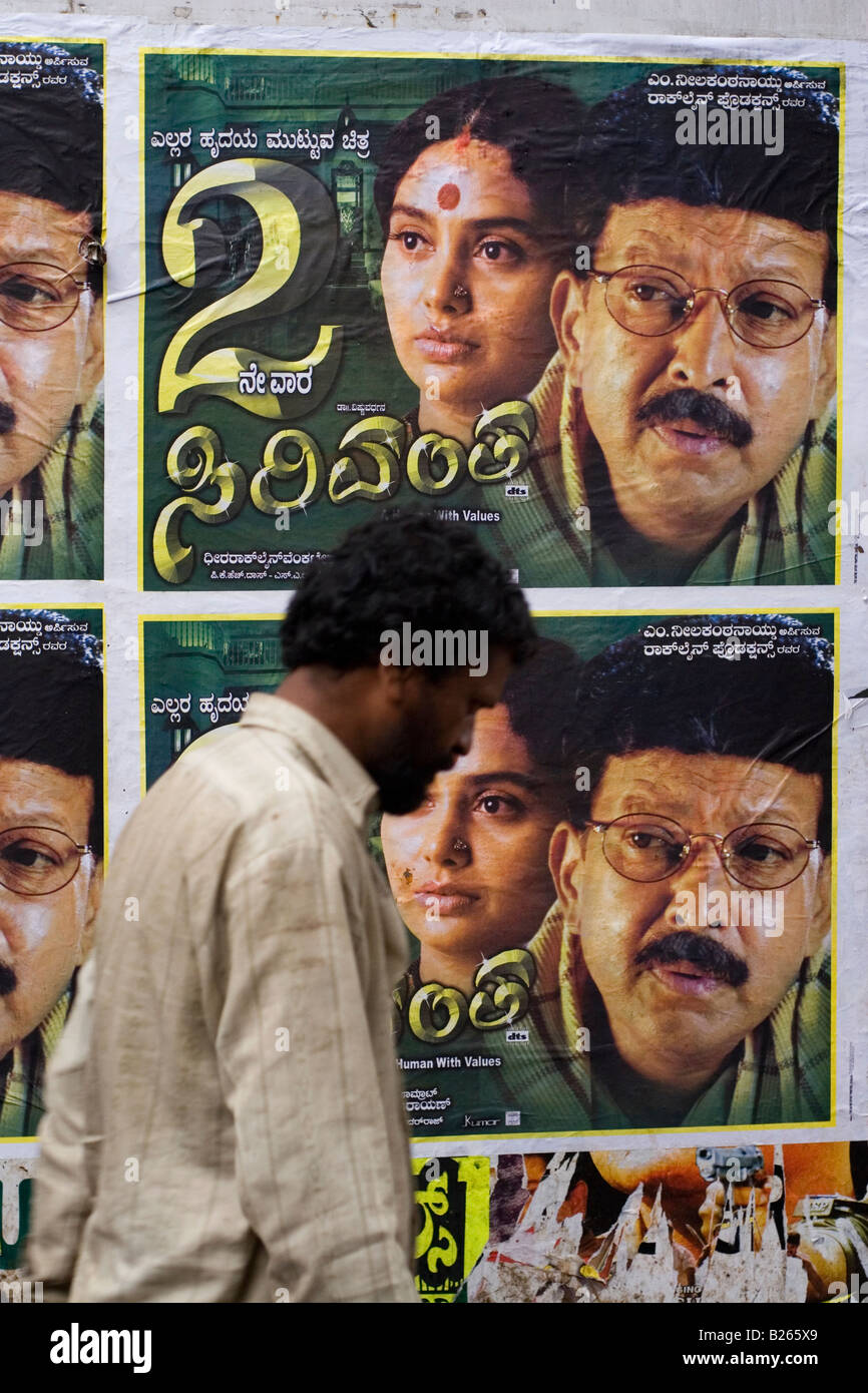 https www alamy com stock photo a man walks past a wall plastered with film posters in bangalore india 18576049 html