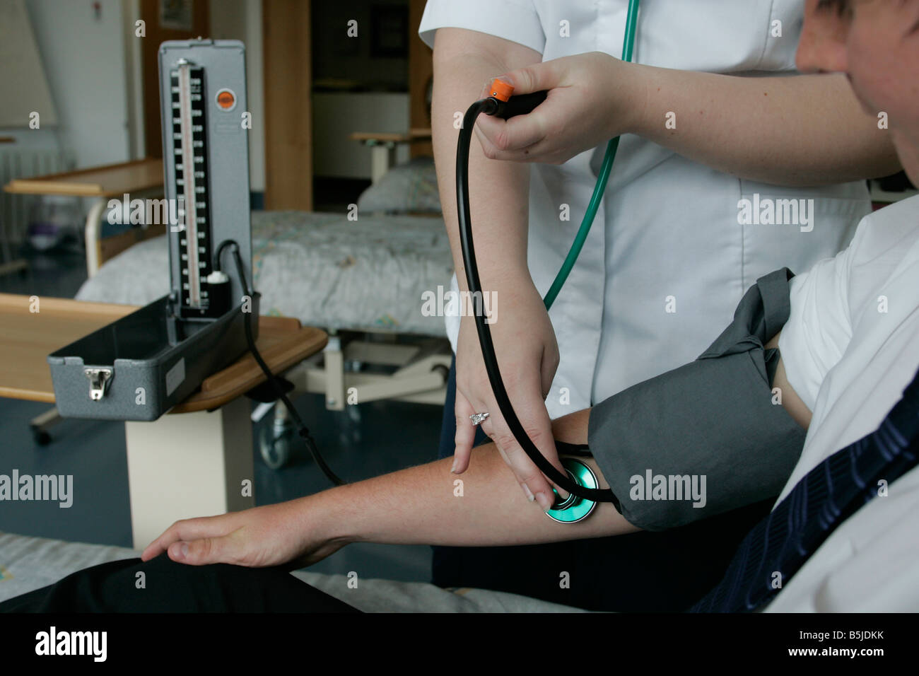 A Student Nurse Taking Someones Blood Pressure On The