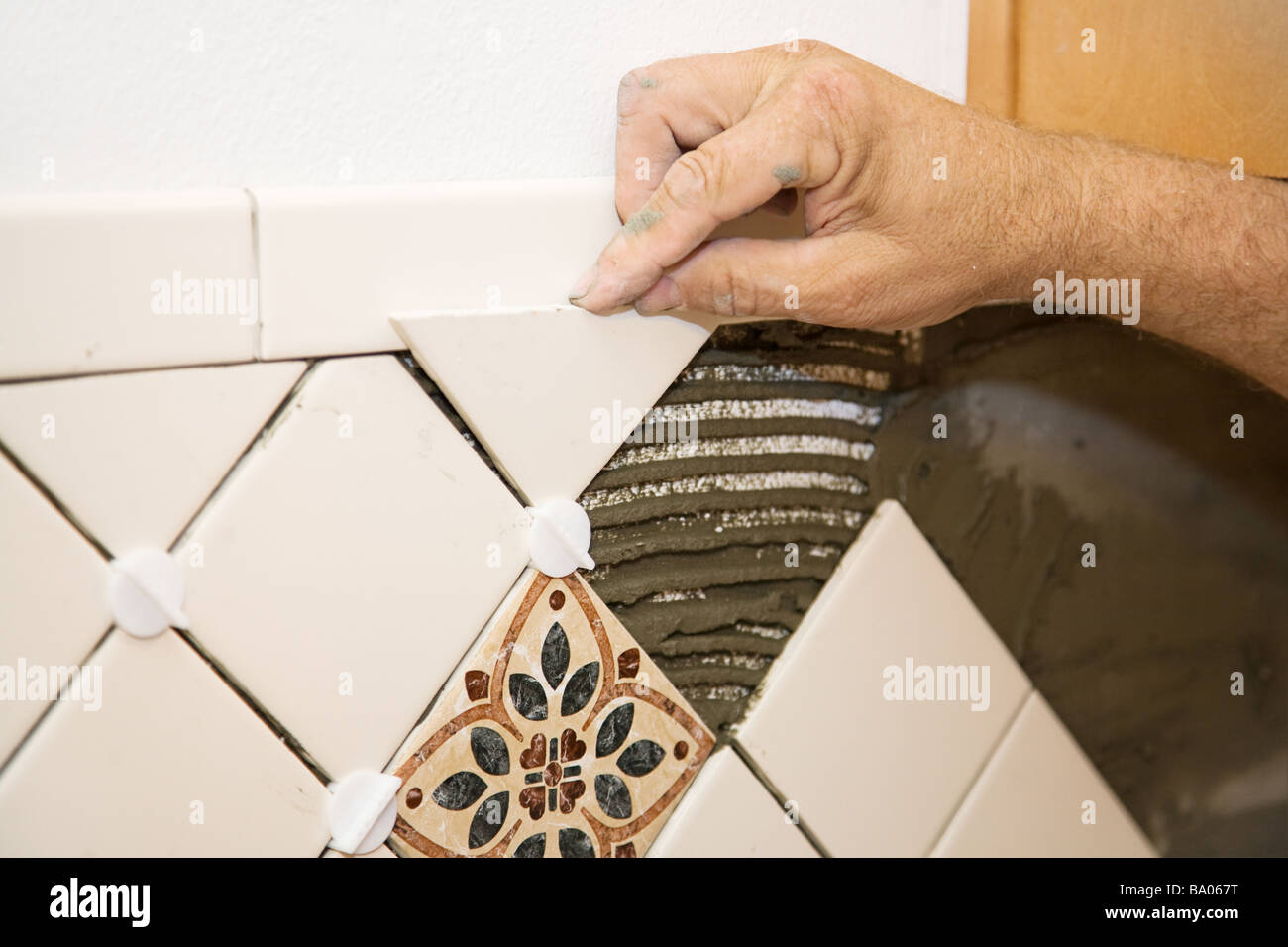 https www alamy com stock photo closeup of a tile setter s hand as he lays out tiles on the wall 23361852 html