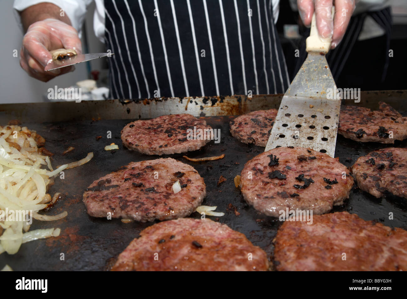 Chef Cooking Hamburgers On An Open Grill Hotplate For Sale
