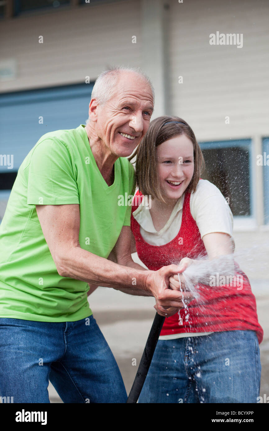 Old Man And Young Girl Washing Car