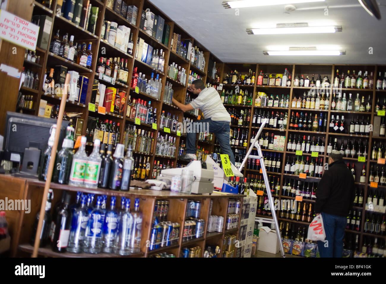 Liquor Store Worker Climbing A Ladder To Shelves In Machane