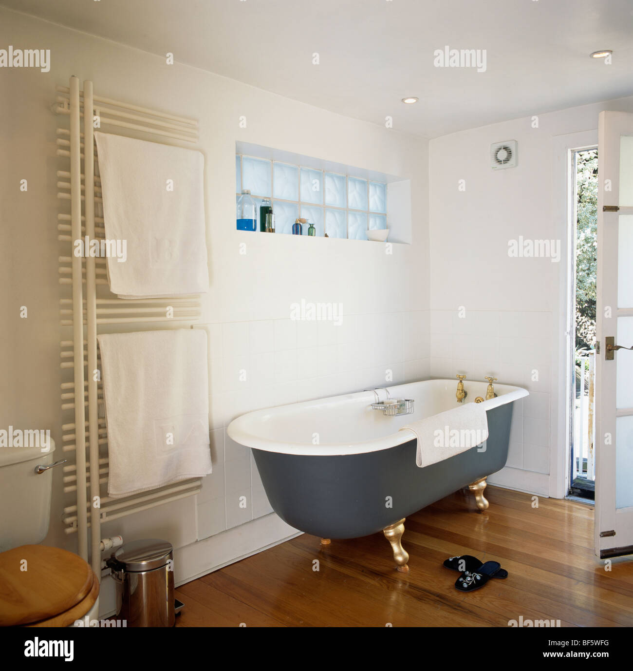 Black Roll Top Bath And Wooden Flooring In Modern White
