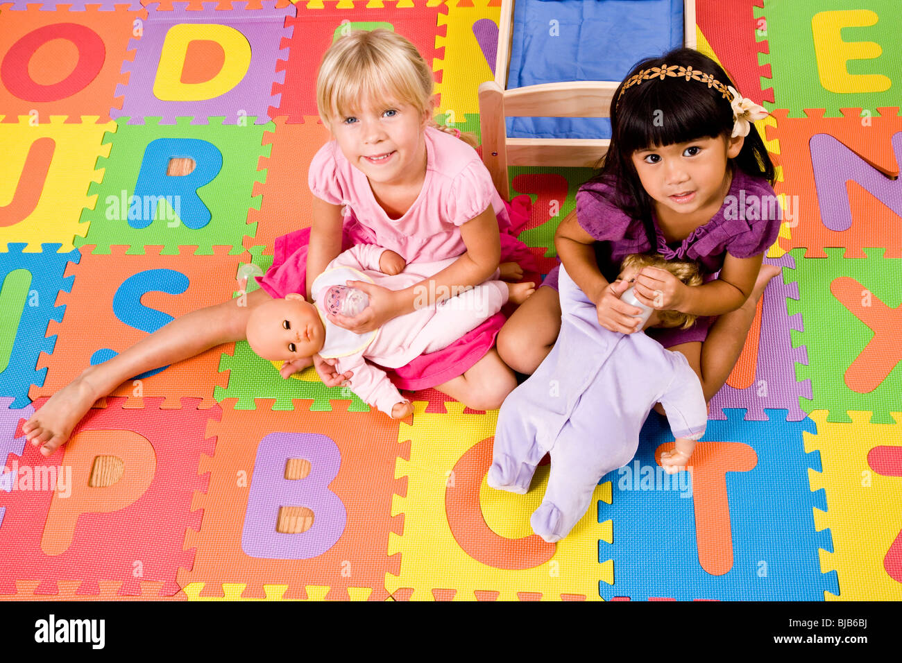 Little Preschool Girls Playing With Dolls On Colorful