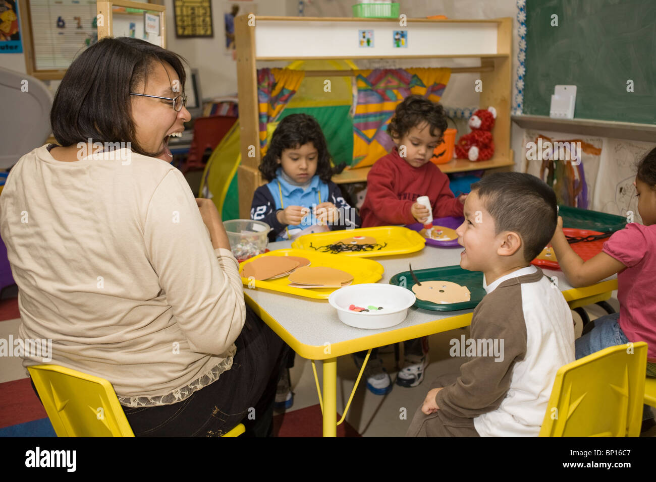 African American Preschool Teacher Laughing With Student