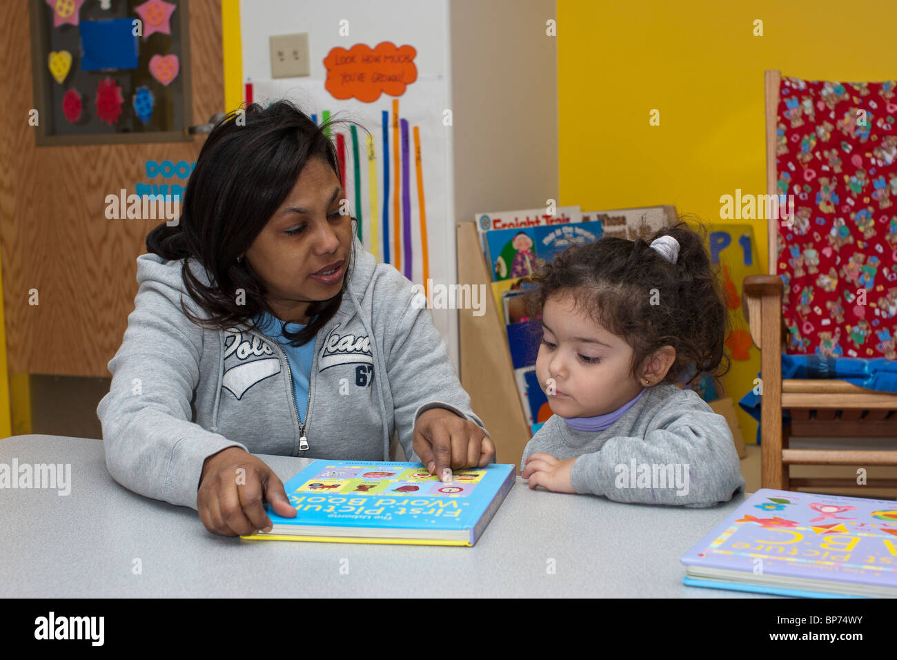 Preschool Teacher Reading A Book With Her 4 Year Old Girl