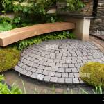 Garden Bench And Stone Patio In Circular Curves With Moss Wall Stock Photo Alamy